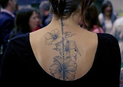 bursting black and white hibiscus flowers with quote tattoo on spine