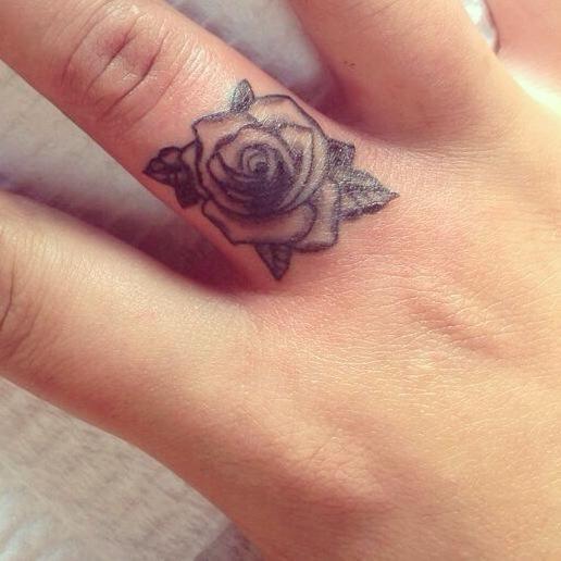 ring finger black and white rose flower tattoo