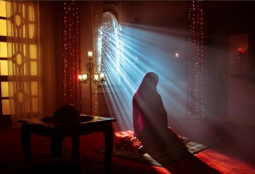muslim woman praying namaz in rays of light
