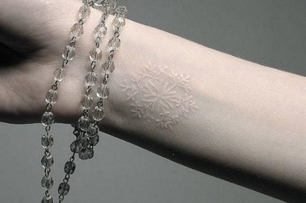 white ink snowflake tattoo on wrist