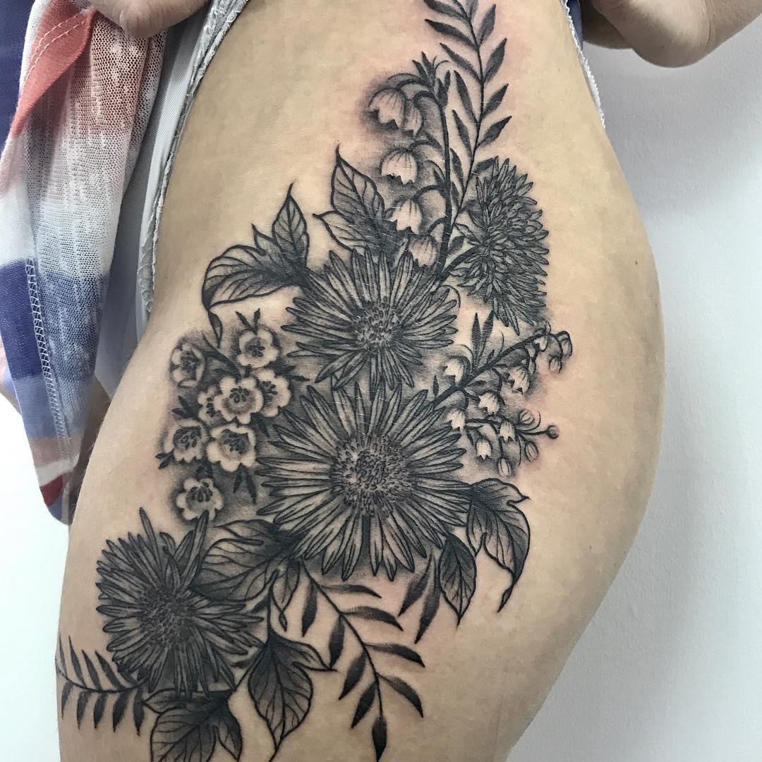 black and white detailed floral tattoo on side thigh