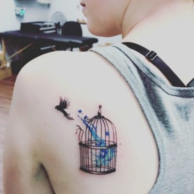 bird flying out of cage tattoo on back shoulder