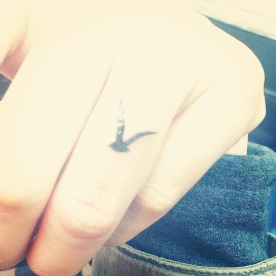 small seagull print tattoo on finger