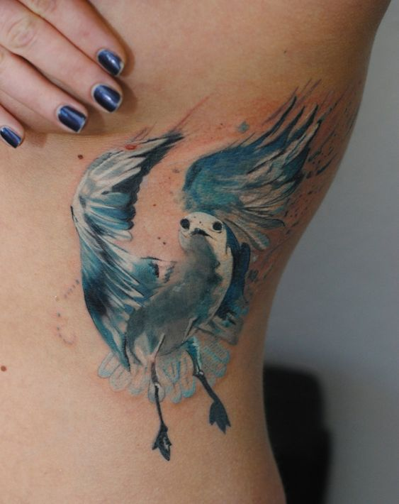 watercolor seagull tattoo on ribs