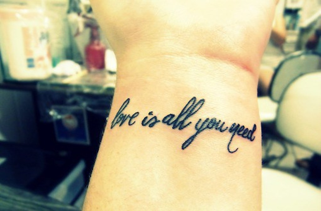 love is all you need tattoo on wrist