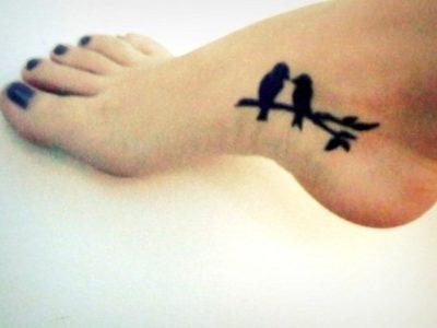 small black ink silhouette lovebirds tattoo on women feet