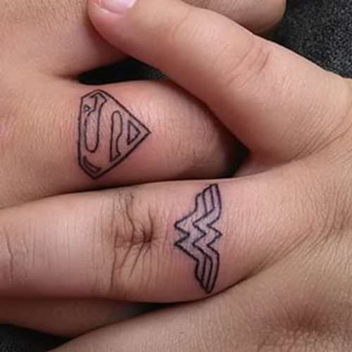 superman and superwoman logo tattoo on ring fingers for couples