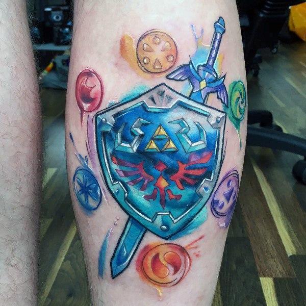 colorful legend of zelda shield tattoo on leg