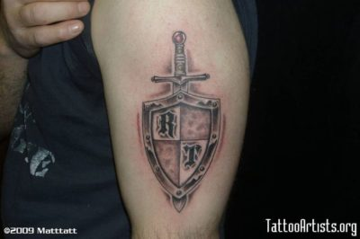 sword armor shield tattoo on upper sleeve