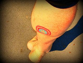 tiny captain america shield tattoo on back of leg