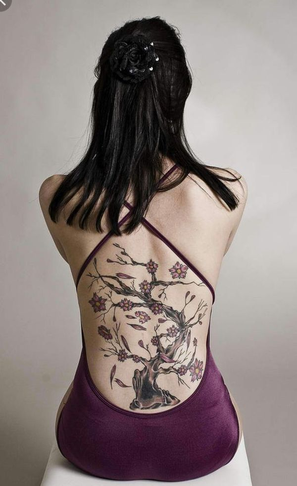 gorgeous lower back female bodhi tree tattoo with pink flowers