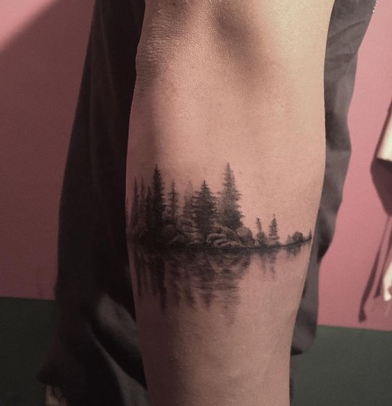 green trees forest reflection tattoo on arm