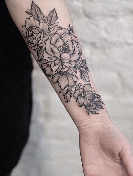 outlined black and grey flower tattoo on forearm