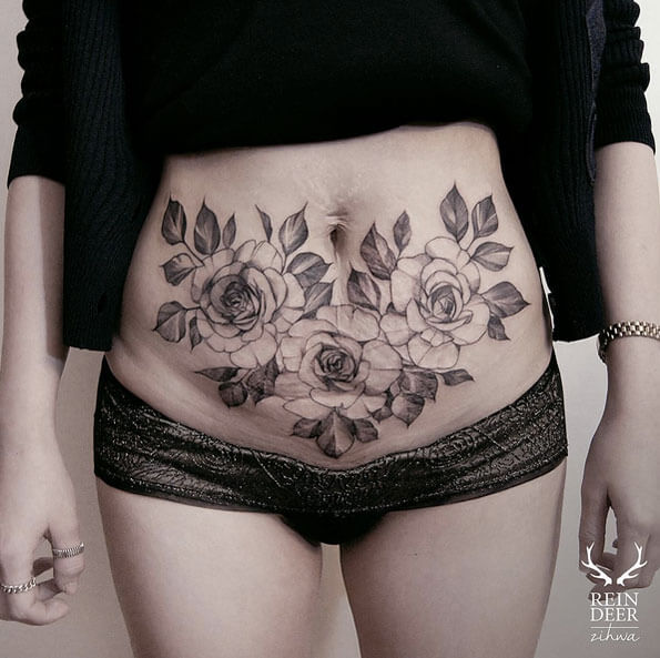 black and grey rose flowers with leaves cover up tattoo on stomach