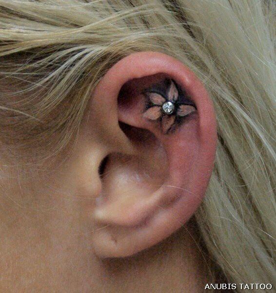 plumeria flower pearcing tattoo on ear