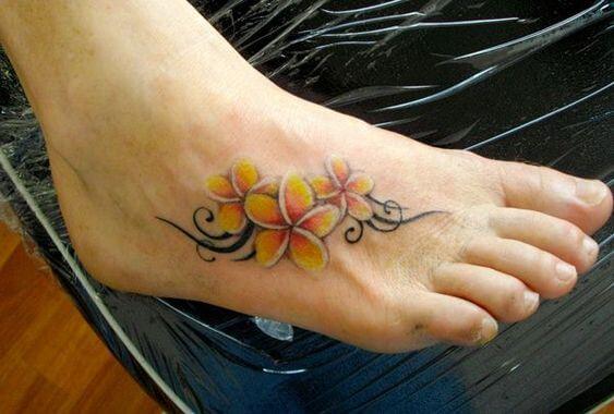 yellow plumeria tribal foot tattoo