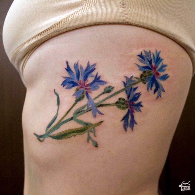 cornflower tattoo design on rib cage for females