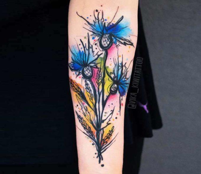 unique watercolor cornflower tattoo design on forearm