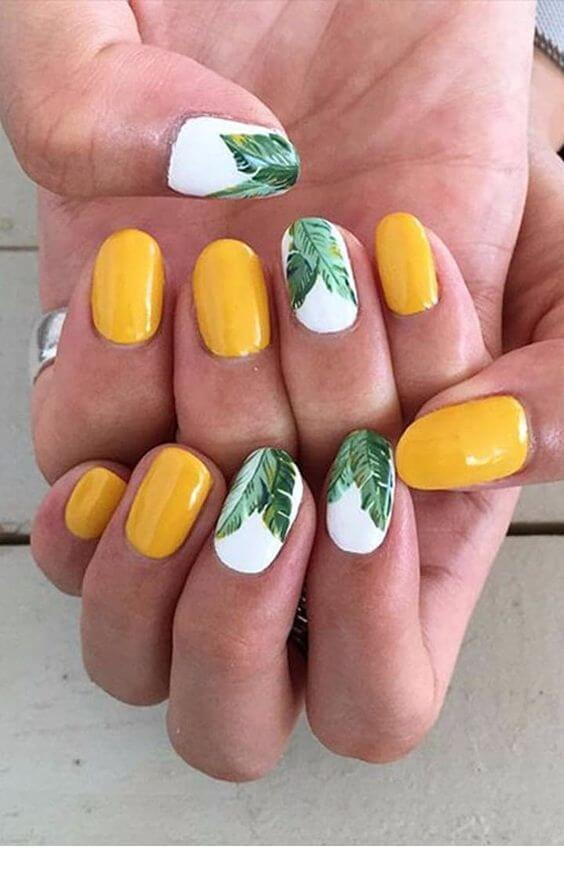 yellow nails with green leaves on white nail polish