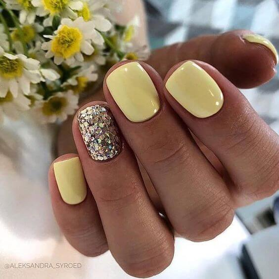 short pale yellow nails with silver glitter designs