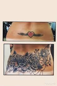 female cover up flower tattoo on lower back