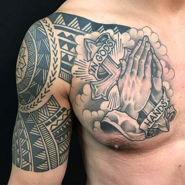 in gods hands banner tattoo with clouds and cross with tribal aztec design on chest shoulder