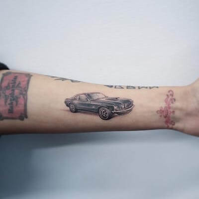 small ford mustang tattoo on forearm