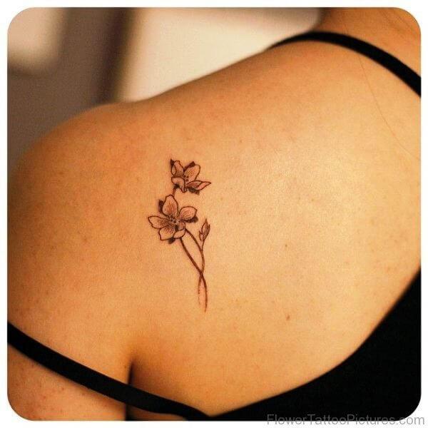 little outline orchid flower tattoo on shoulder blade