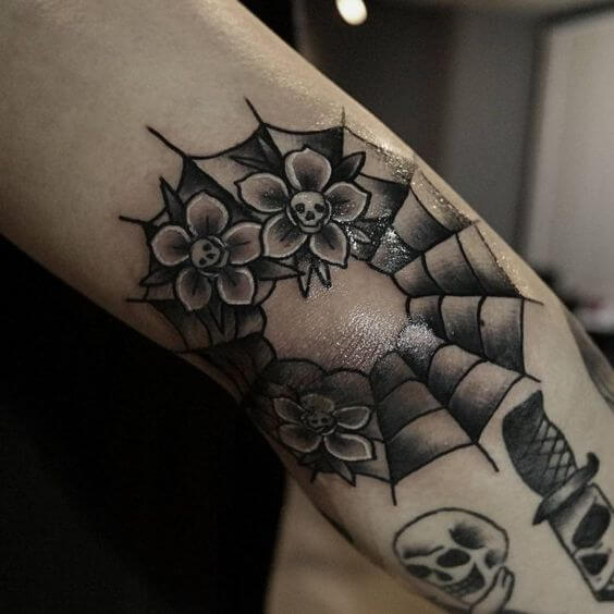 small floral spider web tattoo design on elbow
